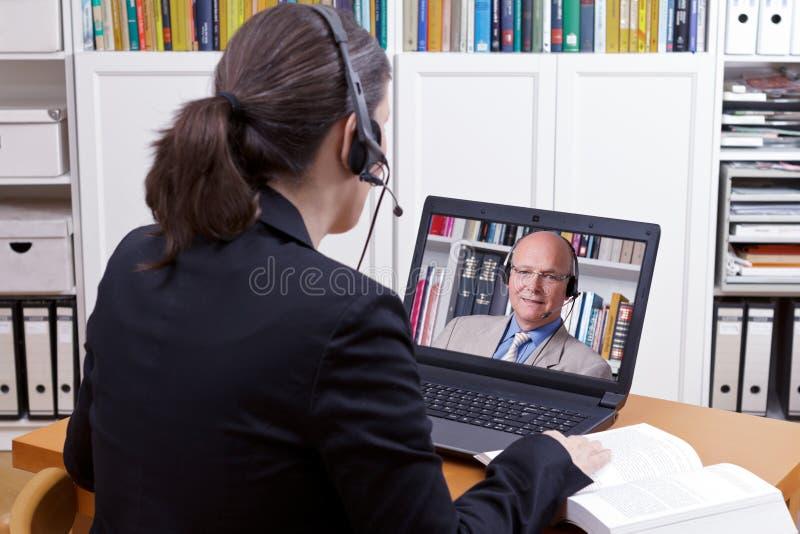 Os auriculares do homem da mulher em linha conversam imagens de stock