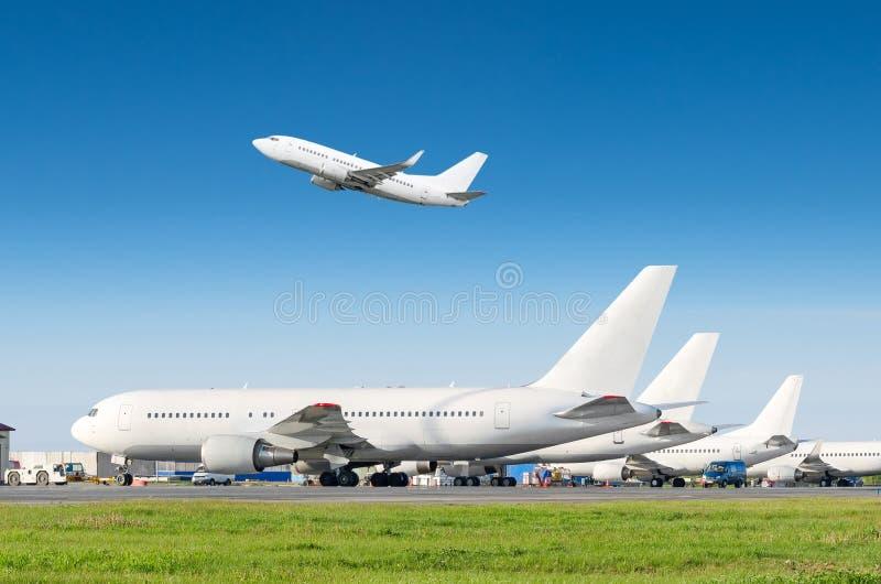 Os aviões de passageiro enfileiram, avião estacionado no serviço antes da partida no aeroporto, o outro plano empurram para trás  foto de stock