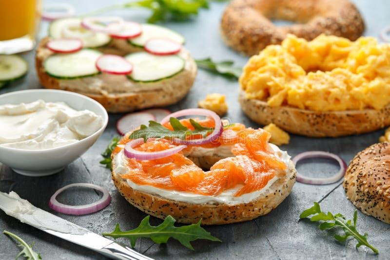Os Bagels saudáveis tomam o pequeno almoço sanduíche com salmões, ovos mexidos, vegetais e queijo creme imagem de stock