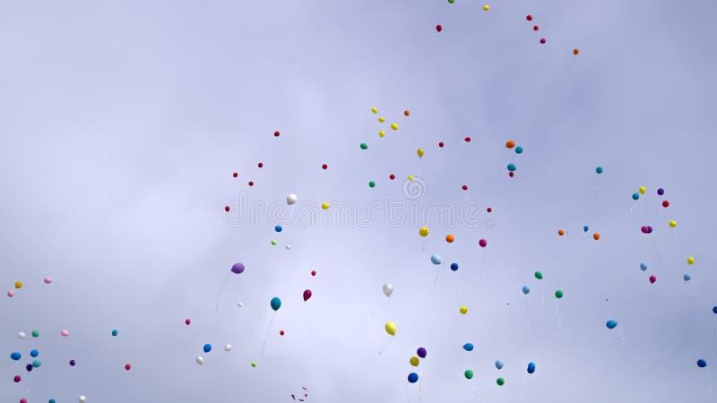Os balões coloridos lançaram-se no céu foto de stock