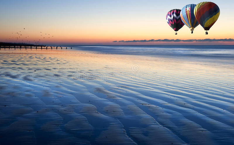 Os balões de ar quente sobre a baixa maré encalham no nascer do sol foto de stock