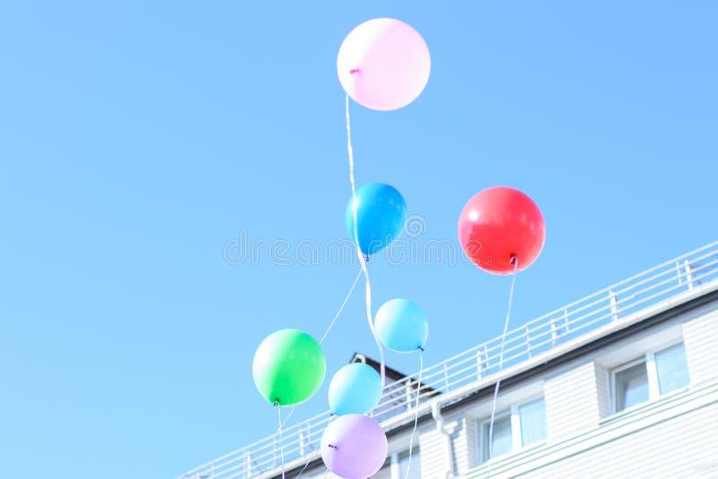 Os balões leves coloridos voam no céu azul, claro Conceito de fotografia de stock royalty free