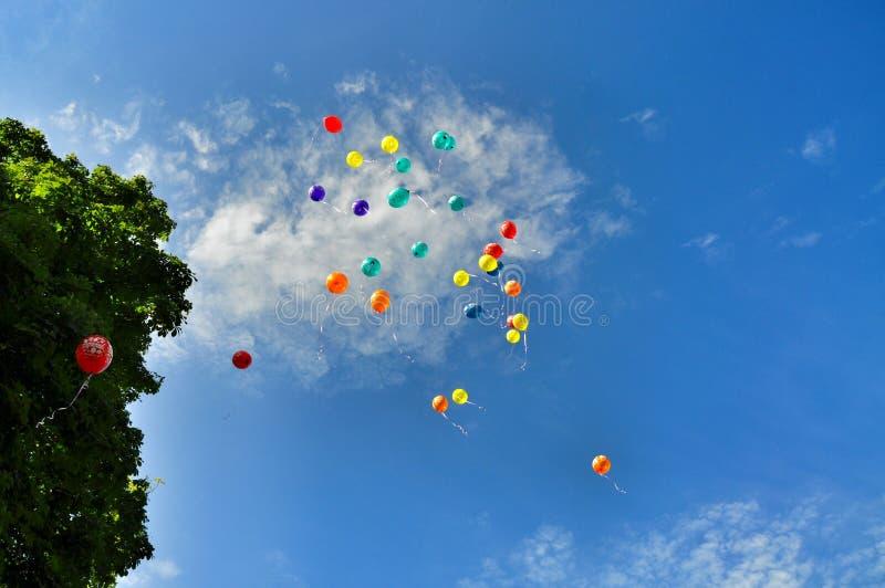 Os balões Multi-coloured partem ao céu imagens de stock royalty free