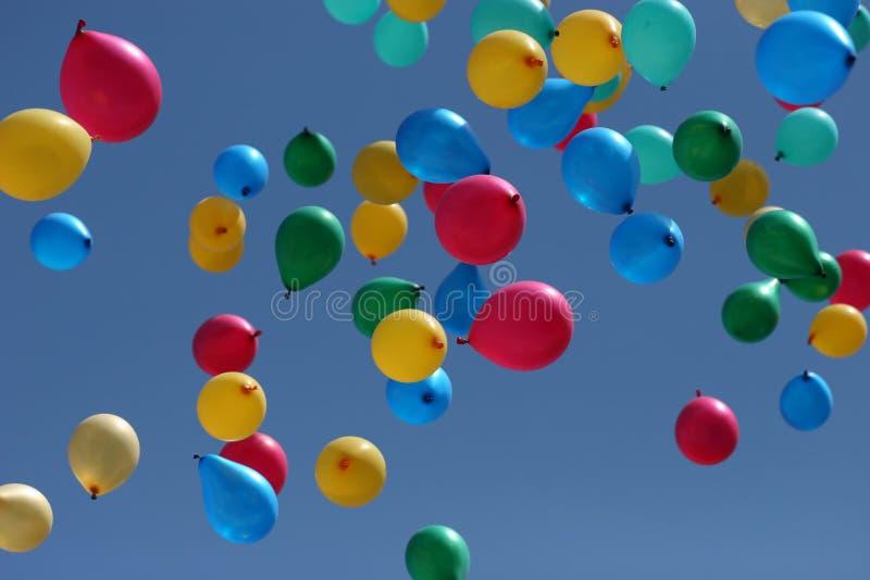 Os balões Multi-coloured partem ao céu foto de stock