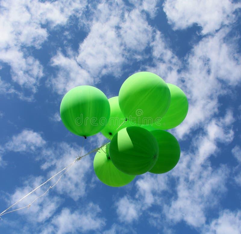 Os balões verdes voam afastado no céu fotografia de stock royalty free