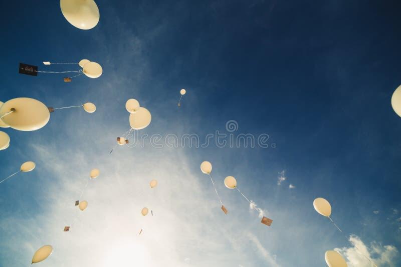 Os bal?es brancos voam acima no c?u azul A libera??o de bal?es festivos nas nuvens Bolas do gel do ar na atmosfera imagem de stock