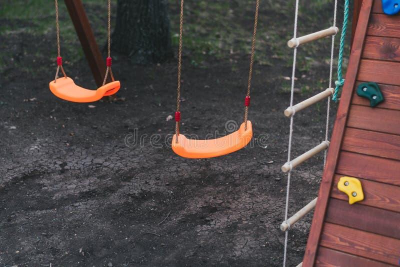 os balanços das crianças em correntes no campo de jogos contra um fundo escuro a laranja das crianças para vacilar terra preta es fotografia de stock
