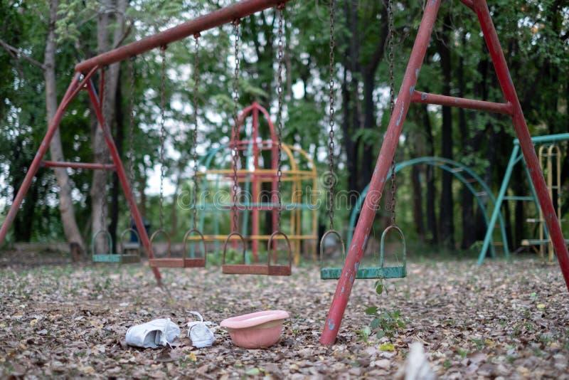 Os balanços das crianças penduram vazio uma quietude em um campo de jogos em um dia maçante, nublado Dia da criança perdida imagem de stock