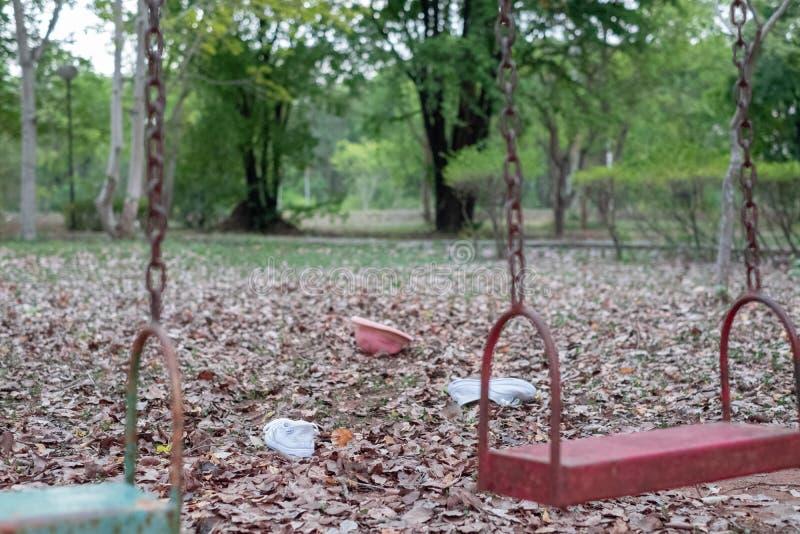 Os balanços das crianças penduram vazio uma quietude em um campo de jogos em um dia maçante, nublado Dia da criança perdida fotografia de stock royalty free