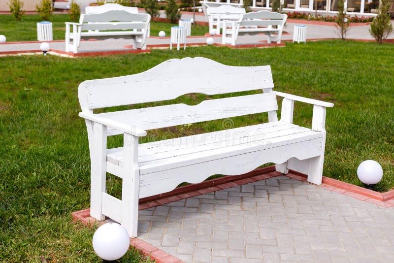 Os bancos vazios de madeira brancos na cidade estacionam fotografia de stock royalty free