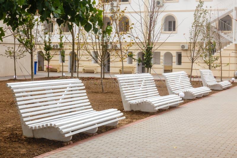 Os bancos vazios de madeira brancos na cidade estacionam fotos de stock