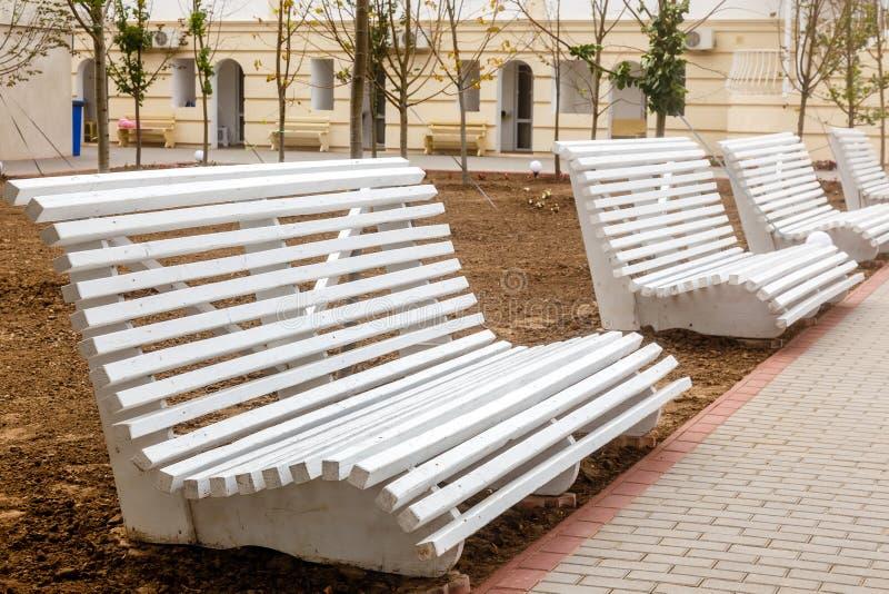 Os bancos vazios de madeira brancos na cidade estacionam imagem de stock
