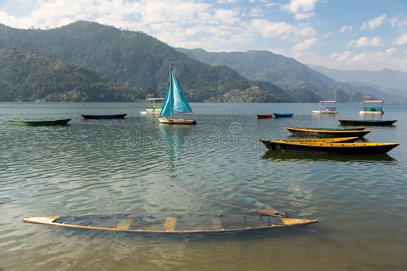Os barcos coloridos dispersaram no Phewa Tal Lake em Pokhara, Nepal imagens de stock royalty free