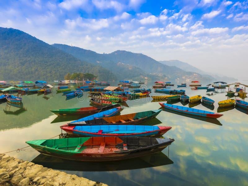 Os barcos com cores diferentes, a reflexão do céu azul na água Vista do lago Phewa foto de stock royalty free