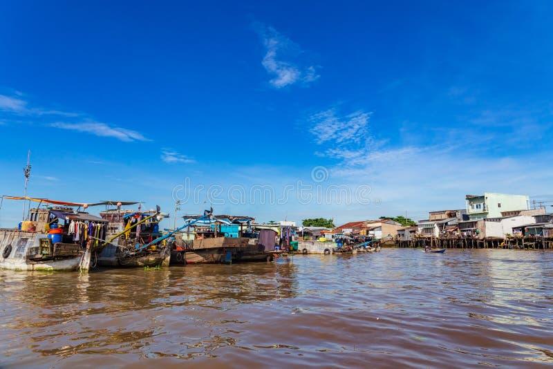 os barcos da Longo-cauda, os barcos de casa e as sampanas amarraram de lado a lado pelas casas de Can Tho, delta de Mekong, Vietn fotos de stock royalty free