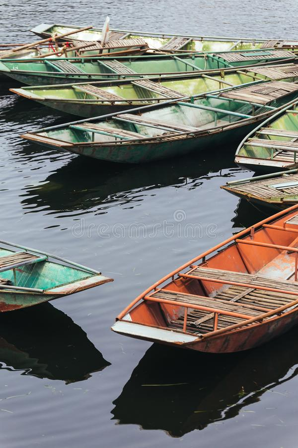 Os barcos de enfileiramento vazios vermelhos e verdes param sobre o rio em Trang grutas em Ninh Binh, Vietname imagem de stock royalty free