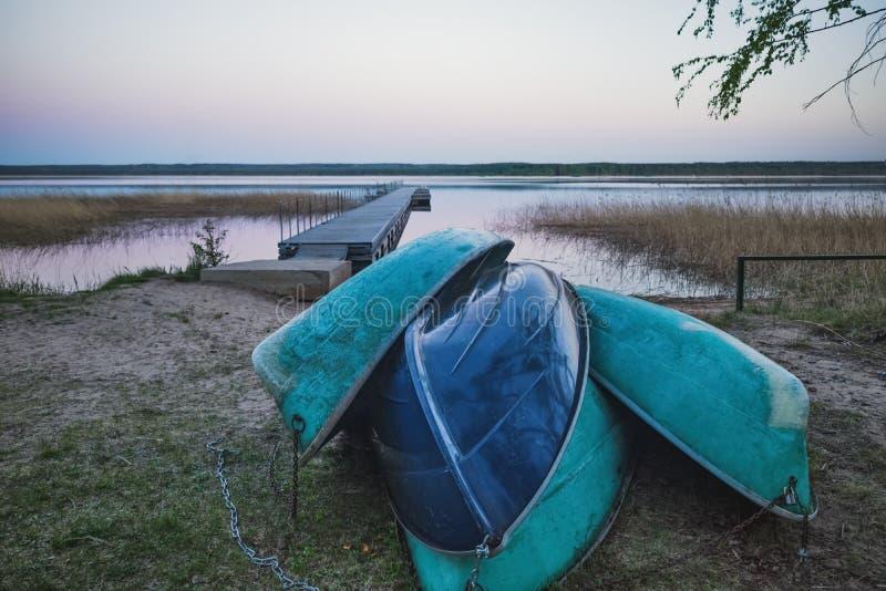 Os barcos de enfileiramento velhos inverteram na costa no fundo do cais e do lago fotos de stock royalty free