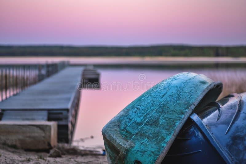 Os barcos de enfileiramento velhos inverteram na costa no fundo do cais e do lago imagem de stock royalty free