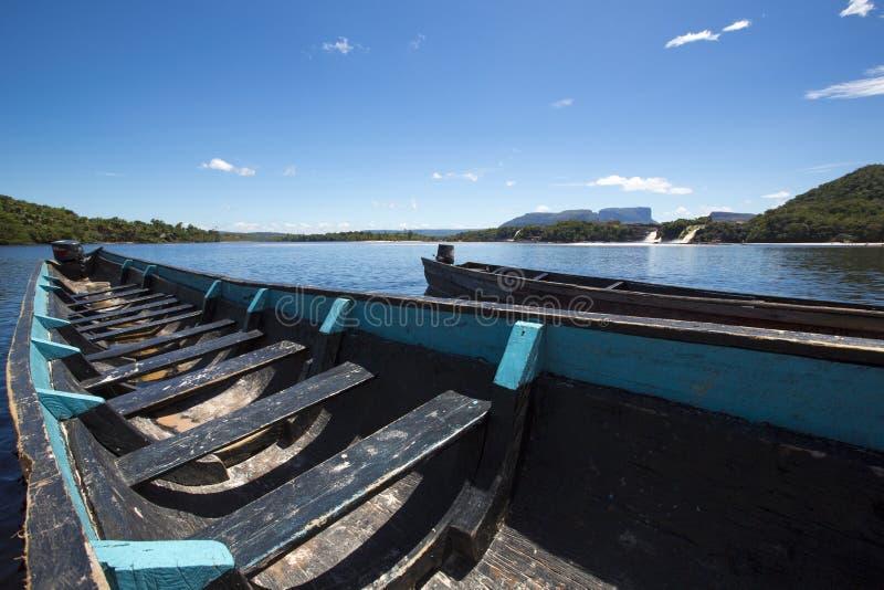 Os barcos de madeira azuis na frente de Hacha caem, Canaima, Venezuela foto de stock