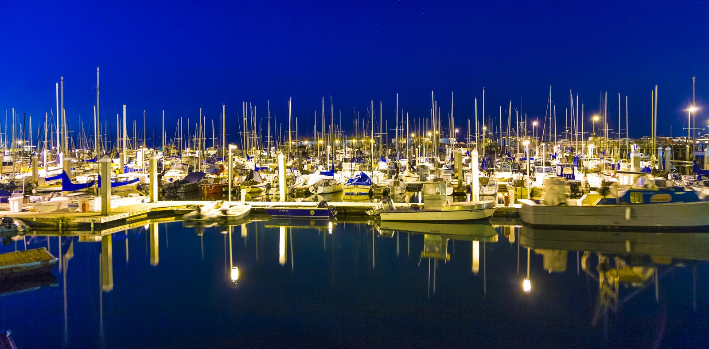 Os barcos de navigação no Monterey sem vento abrigam no cais pelo nig fotografia de stock royalty free