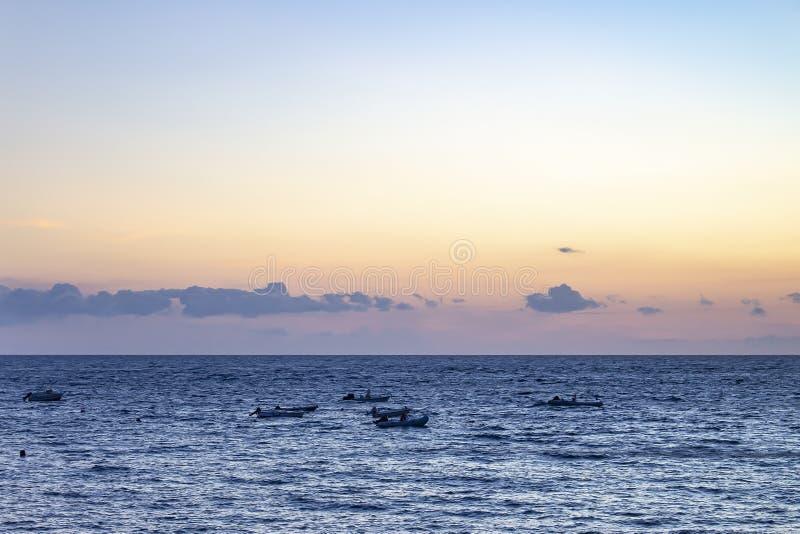 Os barcos de pesca abandonados que derivam no mar durante o por do sol ao longo da costa do La Caleta, Costa Adeje em Tenerife, E fotografia de stock