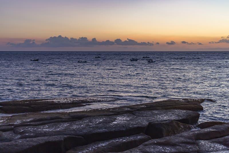 Os barcos de pesca abandonados que derivam no mar durante o por do sol ao longo da costa rochosa do La Caleta, Costa Adeje em Ten imagem de stock