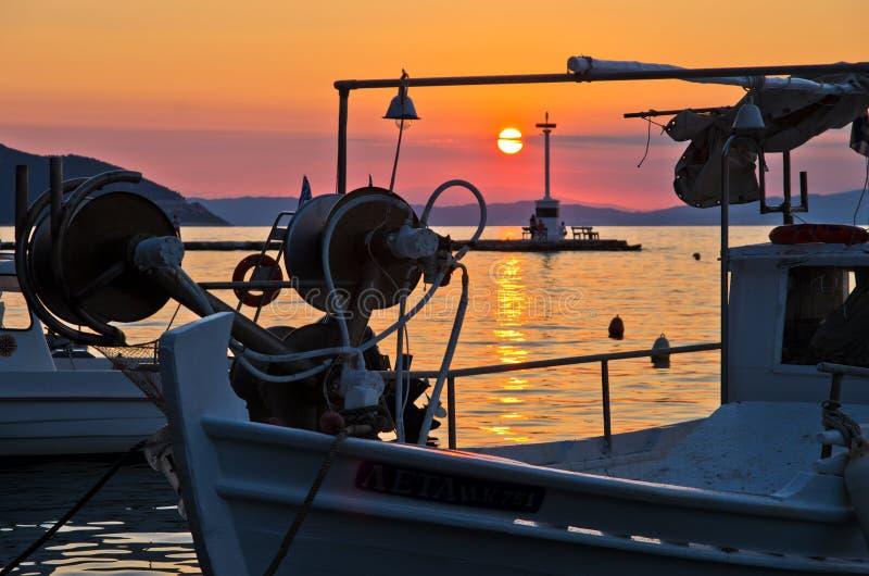 Os barcos de pesca em Limenas abrigam no por do sol, ilha de Thassos foto de stock royalty free