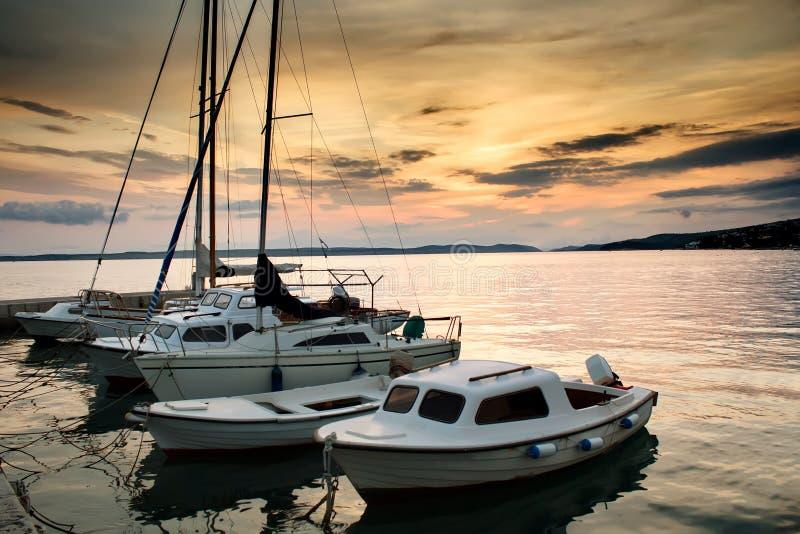 Os barcos de pesca no mar de adriático com por do sol iluminam-se fotos de stock royalty free