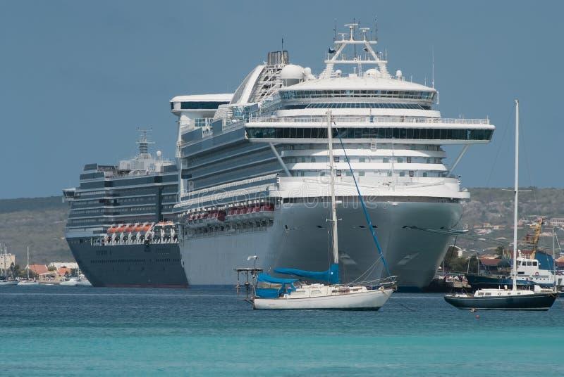 Os barcos de vela e os grandes navios de cruzeiros entraram no porto de Klarendijk fotografia de stock
