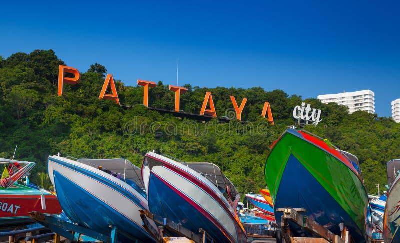 Os barcos e as palavras Pattaya na montanha em Pattaya encalham, Tailândia. fotografia de stock