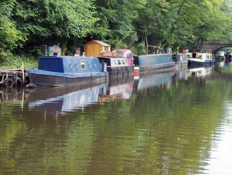 Os barcos estreitos e as barcas amarrados no canal do rochdale hebden dentro a ponte cercada por árvores verdes do verão e por um imagens de stock