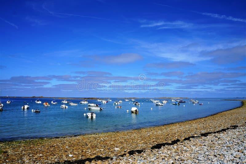 Os barcos que flutuam na água perto do seixos encalham em Brittany fotos de stock