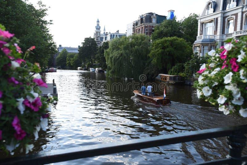 Os barqueiros em um canal de Amsterdão visto de uma ponte alinharam com flores fotografia de stock