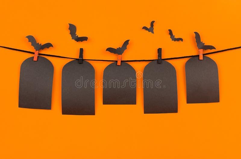 Os bastões do rebanho de Dia das Bruxas e o túmulo vazio preto das etiquetas que penduram em pregadores de roupa, no fundo alaran foto de stock