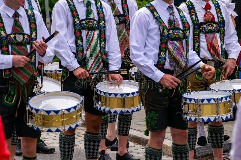 Os bateristas na roupa tradicional puxam cilindros através da cidade imagem de stock