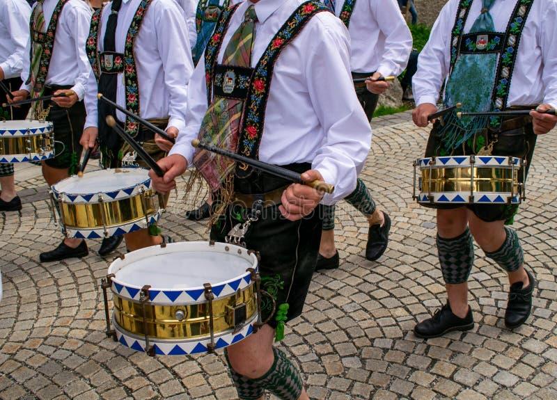 Os bateristas na roupa tradicional puxam cilindros através da cidade fotografia de stock