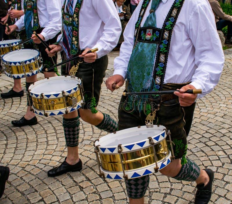 Os bateristas na roupa tradicional puxam cilindros através da cidade foto de stock royalty free