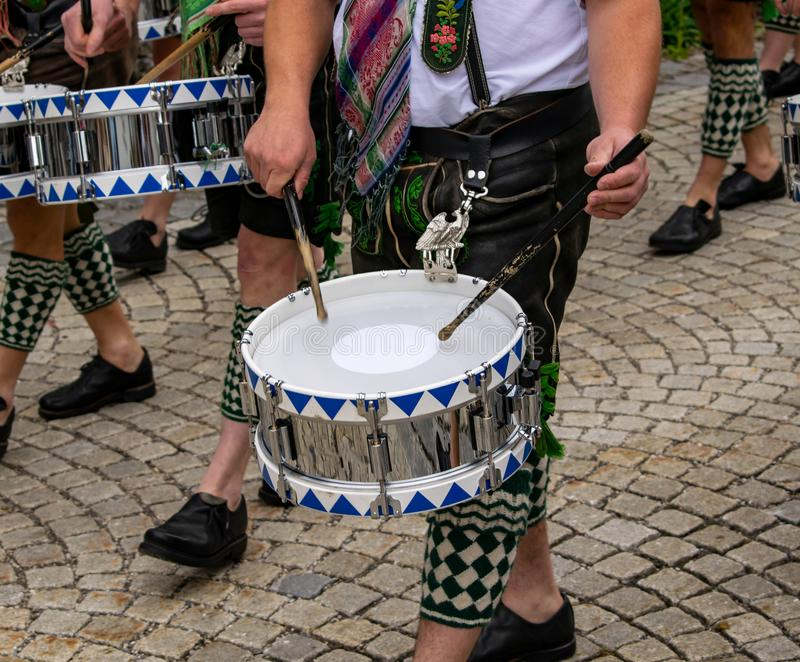 Os bateristas na roupa tradicional puxam cilindros através da cidade foto de stock