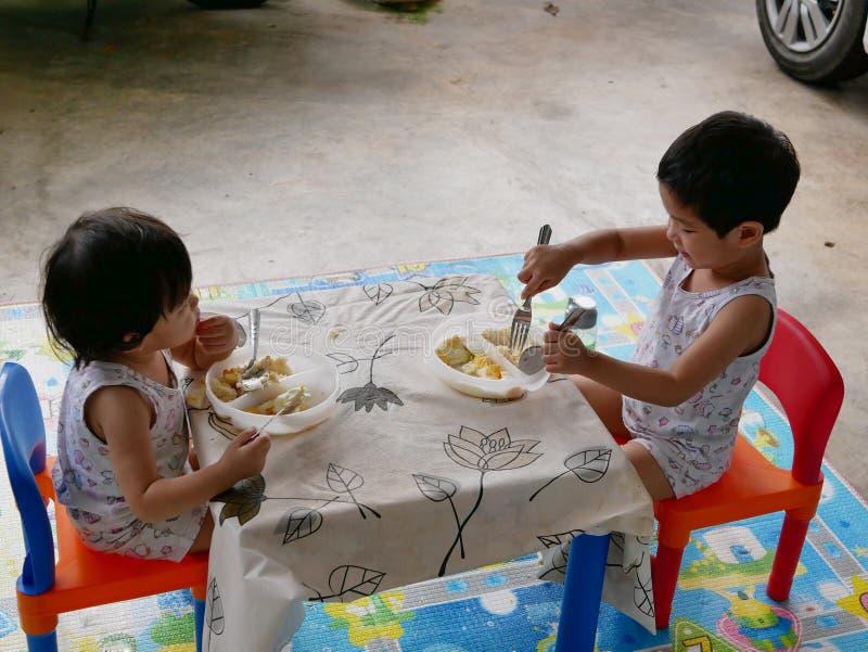 Os bebês asiáticos pequenos apreciam comer o alimento sós fotos de stock royalty free