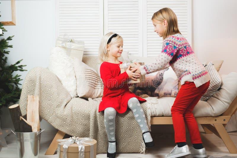 Os bebês da caixa de presente mágica e de uma criança, milagre do Natal, menina de sorriso feliz bonita pequena abrem uma caixa c imagem de stock