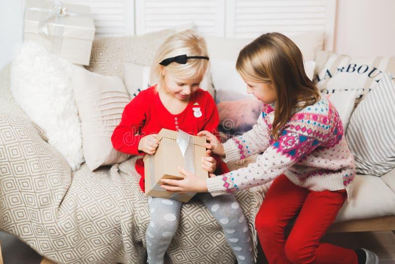 Os bebês da caixa de presente mágica e de uma criança, milagre do Natal, menina de sorriso feliz bonita pequena abrem uma caixa c foto de stock royalty free