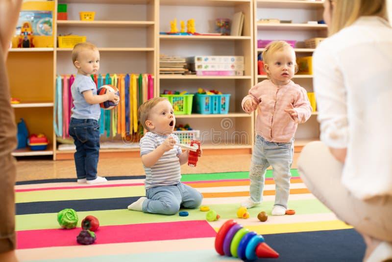 Os bebês do berçário jogam no assoalho com equipes de tratamento ou nas mães no centro de centro de dia imagem de stock