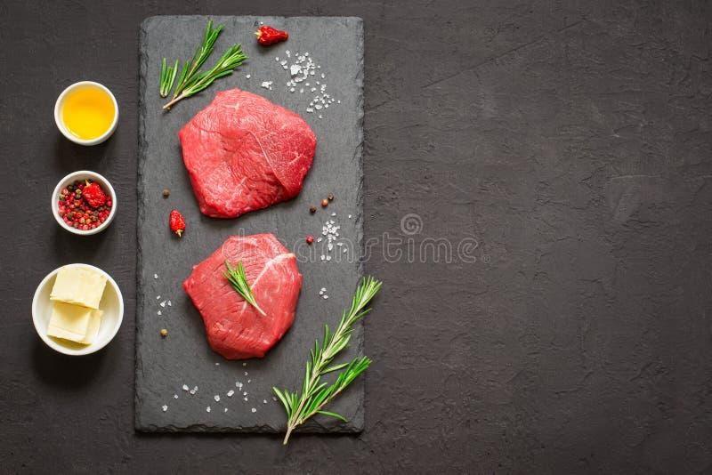 Os bifes da carne crua na ardósia preta embarcam, especiarias e ingrediente fotografia de stock royalty free