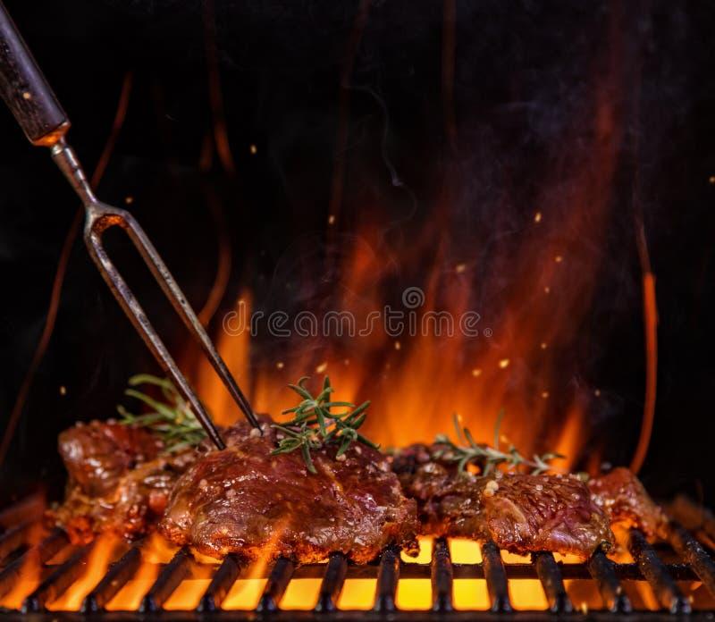 Os bifes na grade raspam, chamas no fundo foto de stock