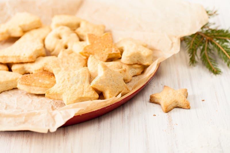 Os biscoitos cozidos frescos no papel do cozimento com abeto ramificam no branco fotos de stock royalty free