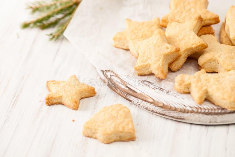 Os biscoitos cozidos frescos no papel do cozimento com abeto ramificam no branco foto de stock