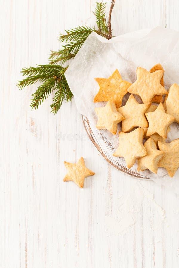 Os biscoitos cozidos frescos no papel do cozimento com abeto ramificam no branco fotografia de stock