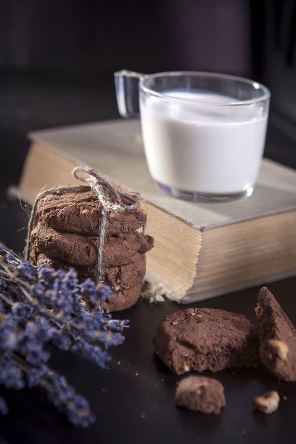 Os biscoitos escuros do chocolate com as porcas no fundo de madeira escuro imagem de stock royalty free
