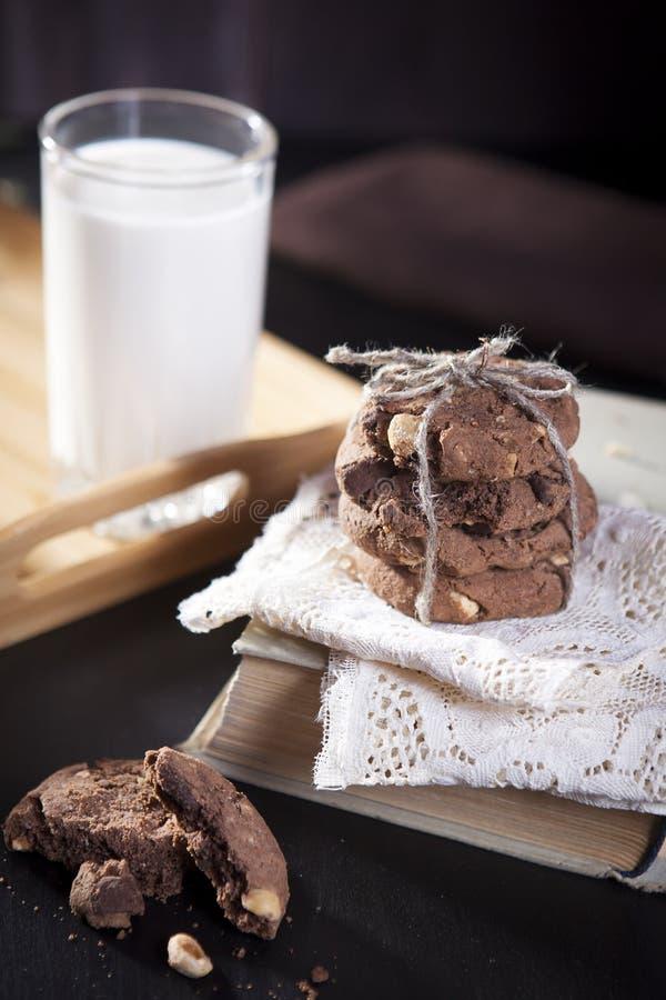 Os biscoitos escuros do chocolate com as porcas no fundo de madeira escuro fotos de stock royalty free