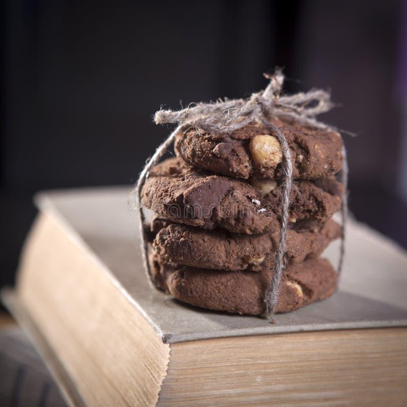 Os biscoitos escuros do chocolate com as porcas no fundo de madeira escuro foto de stock royalty free